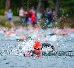 Swimrunner i mitten som simmar i ledning på Skatås sjöar foto Mikael Svensson